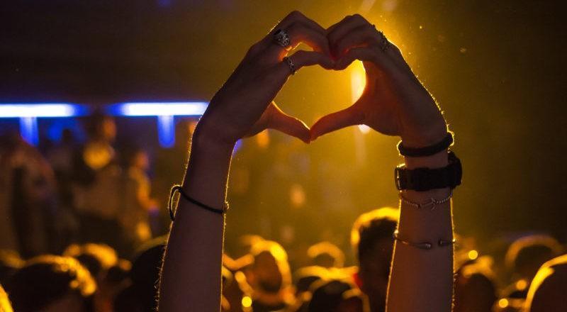 Mani a cuore in un concerto scoperto tramite siti di prenotazione eventi
